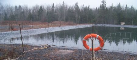 "Frack waste pond in Kennetcook. NS Environment tells the community it is monitoring the ponds. But they are supposed to have 1 metre [39""] of freeboard. There is now less than 12 inches between the surface and overflow, with freeze-up and winter precipitation to add. There are holes in the pond liner right at the water level. Leaks there will flow through the berm above the surrounding ground level."