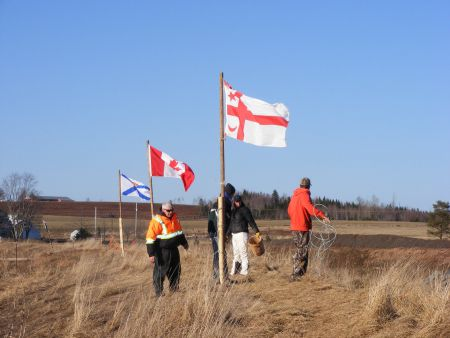 Hardy souls on a COLD day plant Mi'kmaq, Canadian, and Nova Scotia flags at the river discharge site.