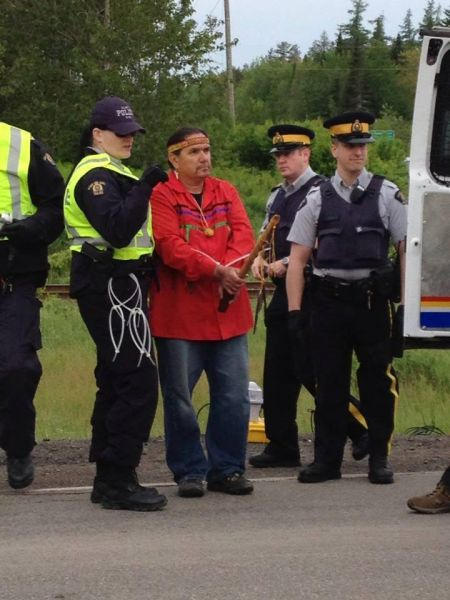 Ron Tremblay, holding sacred pipe, is arrested. Photo courtesy of @1tnb