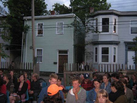 The audience gathers in the Fuller Terrace backyard.