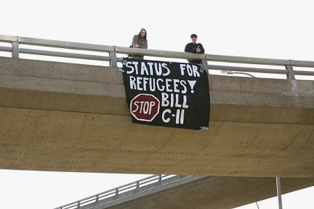 Members of No One Is Illegal defend refugee rights with a banner hung from an overpass. Photo by Hilary Beaumont