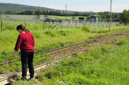 Penobsquis resident Heather McCabe inspects the railway tracks which run by a gas well.
