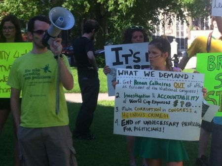 Igor Santos addresses passersby with a list of demands for the Brazilian government. Photo Jon Grant