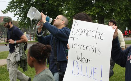 """Isaac Saney chants """"education, not criminalization"""" into the megaphone Saturday (Photo: Hilary Beaumont)"""
