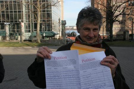 Marike Findley, president of APES, with petition. [Photo: Miles Howe]