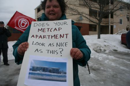 ACORN Nova Scotia member and MetCap tenant Lisa Fairn. The sign includes a photo of what ACORN believes to be the three-garage home of MetCap property manager Teddy Zaghloul. Photo Robert Devet