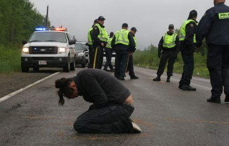 Susanne Patles in prayer, as New Brunswick RCMP confer. [Photo: M. Howe]