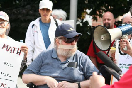 Poverty activist Wayne MacNaughton was gagged to symbolize the sense that government isn't listening. Photo Robert Devet