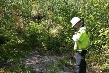 Security guard prays for Mother Nature at the site of a wetlands shot-hole. [Photo: Miles Howe]