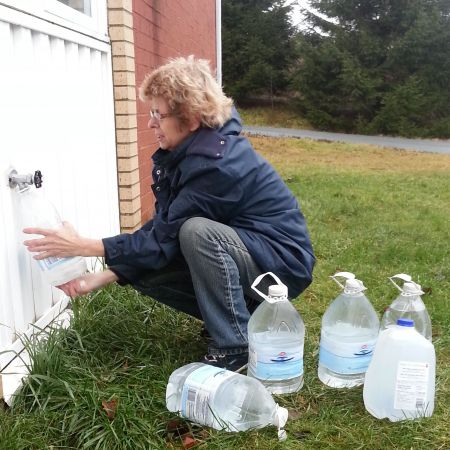 Marlene Brown fills water jugs at St. Paul's Church in Spryfield.