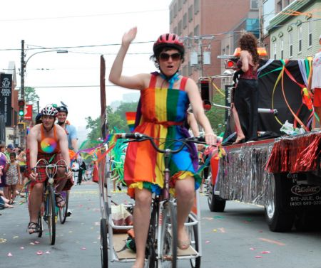 Megan Leslie rides her bike during a pride parade in Halifax (Photo by Gwyneth Dunsford).