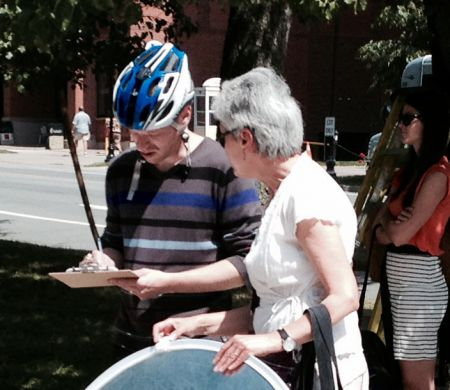 Violet offers a person on a bike the chance to sign a letter to the PM