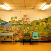 Giraffes roam through a jungle oasis of grassland and waterfalls on a large mural inside the school's front entrance. Community members gather in the foreground, dressed in vibrant prints and head coverings. Grass huts stand in the shade of tall palm trees in the distance. The mural represents St. Pat's Africentric leanings.