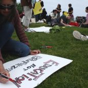 One protester finishes her sign at the commons before joining the march (Photo: Hilary Beaumont)