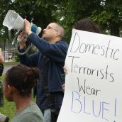Isaac Saney, a Dalhousie faculty member, yells into the megaphone (Photo: Hilary Beaumont)