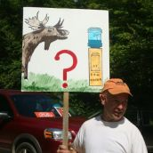A man draws attention to the impacts of shale gas activity on water and wildlife with his sign at the blockade of seismic vibrators in Stanley. Photo: Carla Gunn.