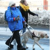 Organizer Kaleigh Trace assists a vision-impaired participant in the rally.
