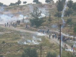 Demonstrators at the weekly non-violent protest in Bil'in village are met with volleys of tear gas launched by Israeli Defence Forces. Despite IDF regulations, soldiers shoot high velocity tear gas canisters directly at protesters, causing an Israeli protester to suffer a fractured skull and internal bleeding on April 23, 2010.