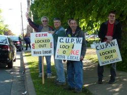 CUPW strikers wave to honking traffic at the community support rally on Thursday.
