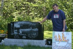 Reggie Pitre stands beside the tombstone of his cousin. [Photo: M. Howe]