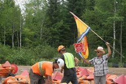 Activists and industry. While SWN-contracted workers load geo-phone bags, one man waves New Brunswick flag. [Photo: M. Howe]
