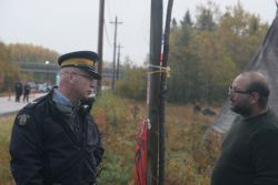 Jason Augustine, District War Chief of Signigtog, speaks to an RCMP officer on October 17th. [Photo: M. Howe]
