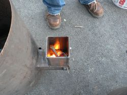 A characteristic of rocket stoves: the fire goes down, into the burn chamber, due to the draw
