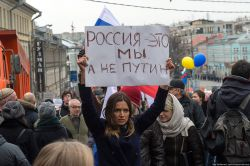 "The placard held by this Russian woman participating in a peace march in Moscow, says ""We are Russia - not Putin."""
