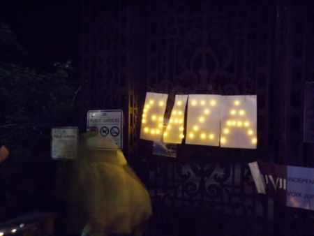 Young woman at vigil looks at homemade sign by Larry Haiven, Gaza in tea lights